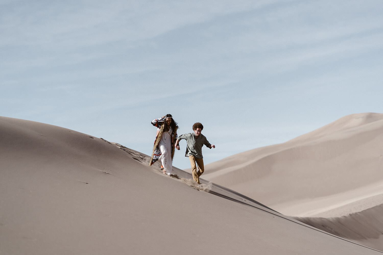 Bride and Groom running at Colorado Great Sand Dunes Elopement