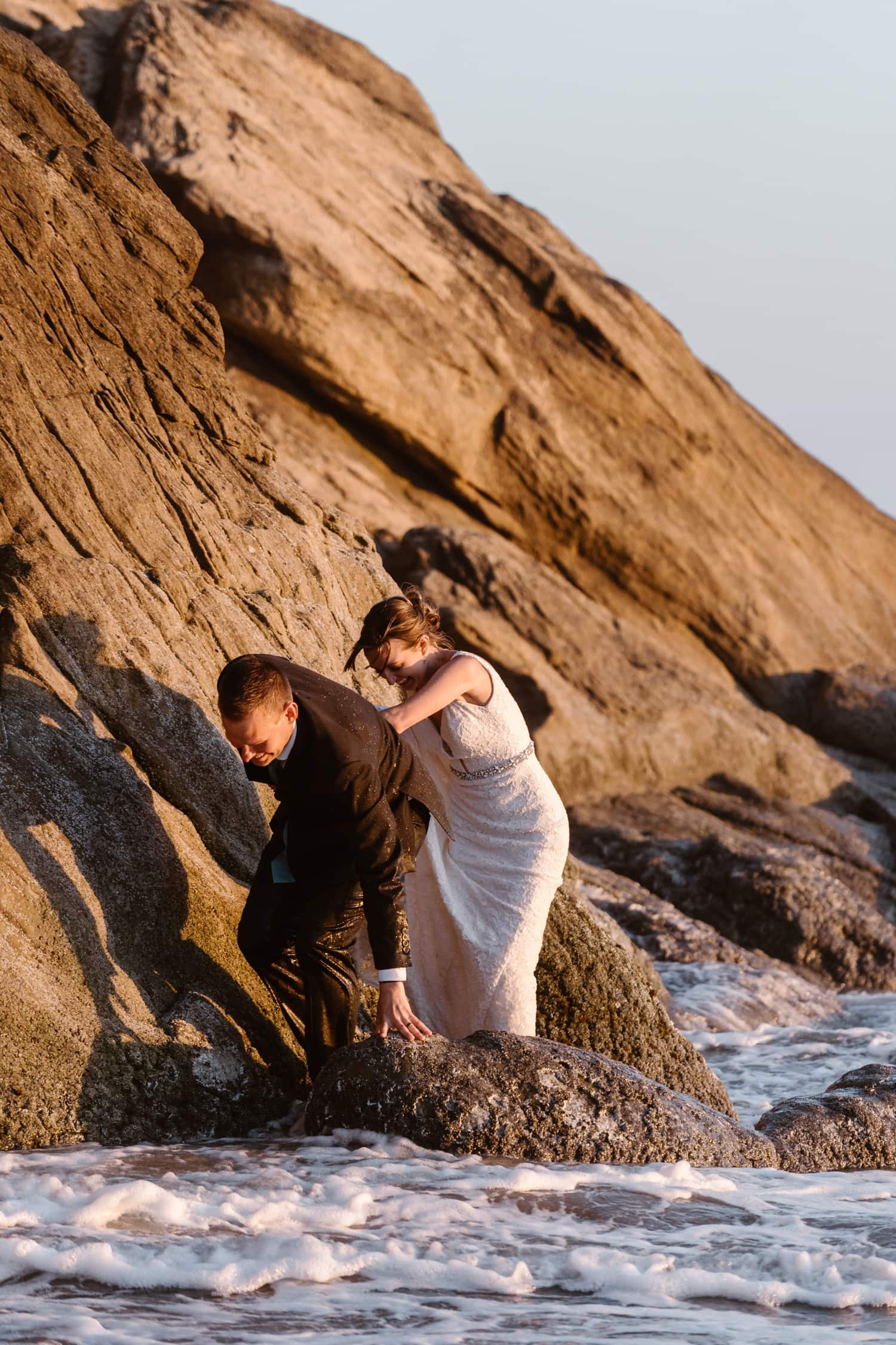 Bride and Groom climbing on rock at Hug Point & Cannon Beach Elopement