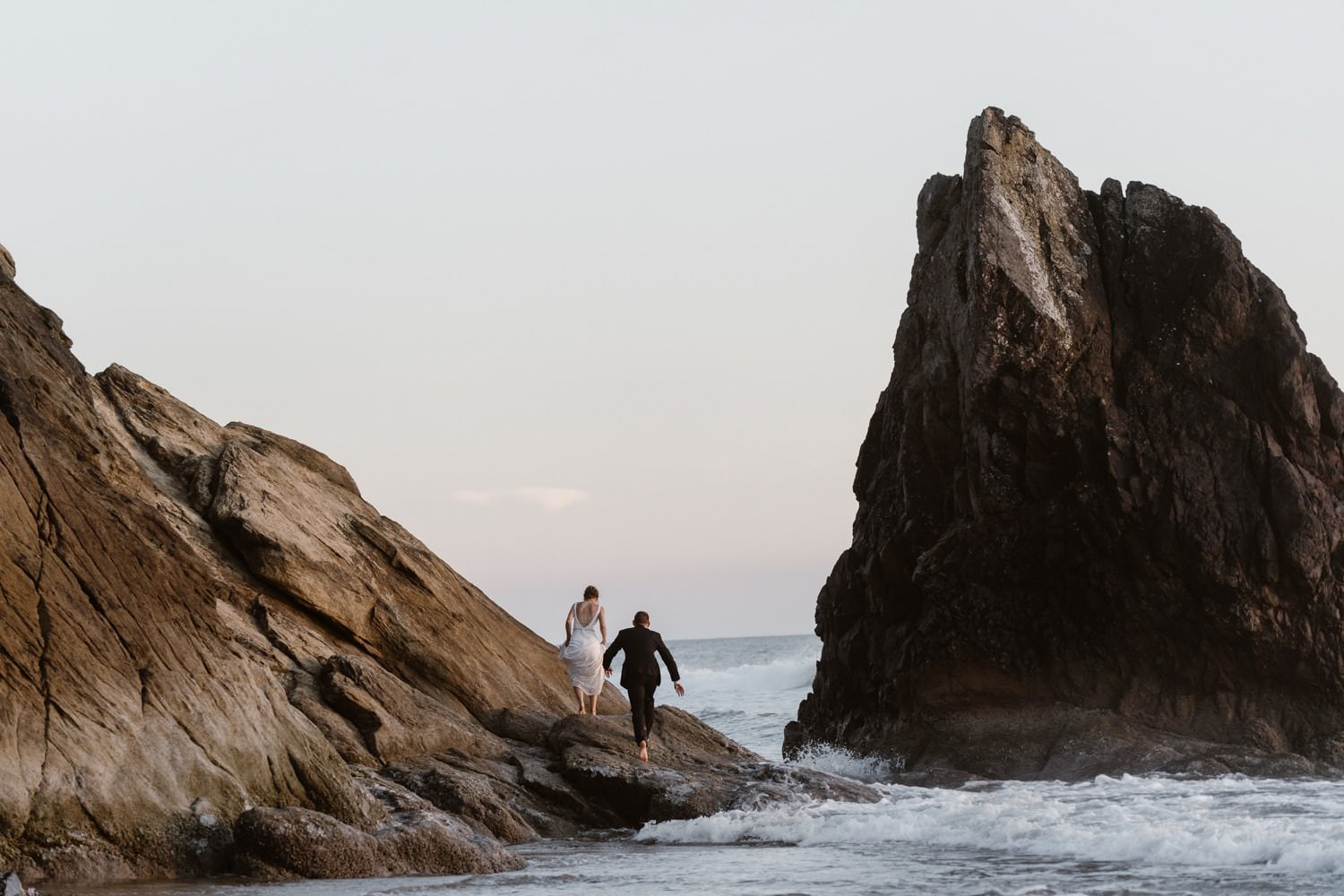 Bride and Groom climbing rock at Hug Point & Cannon Beach Elopement