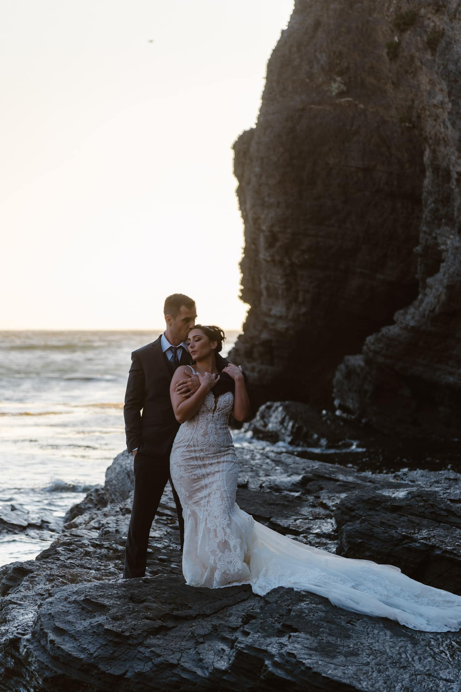 Groom kissing bride at sunset at Big Sur Elopement