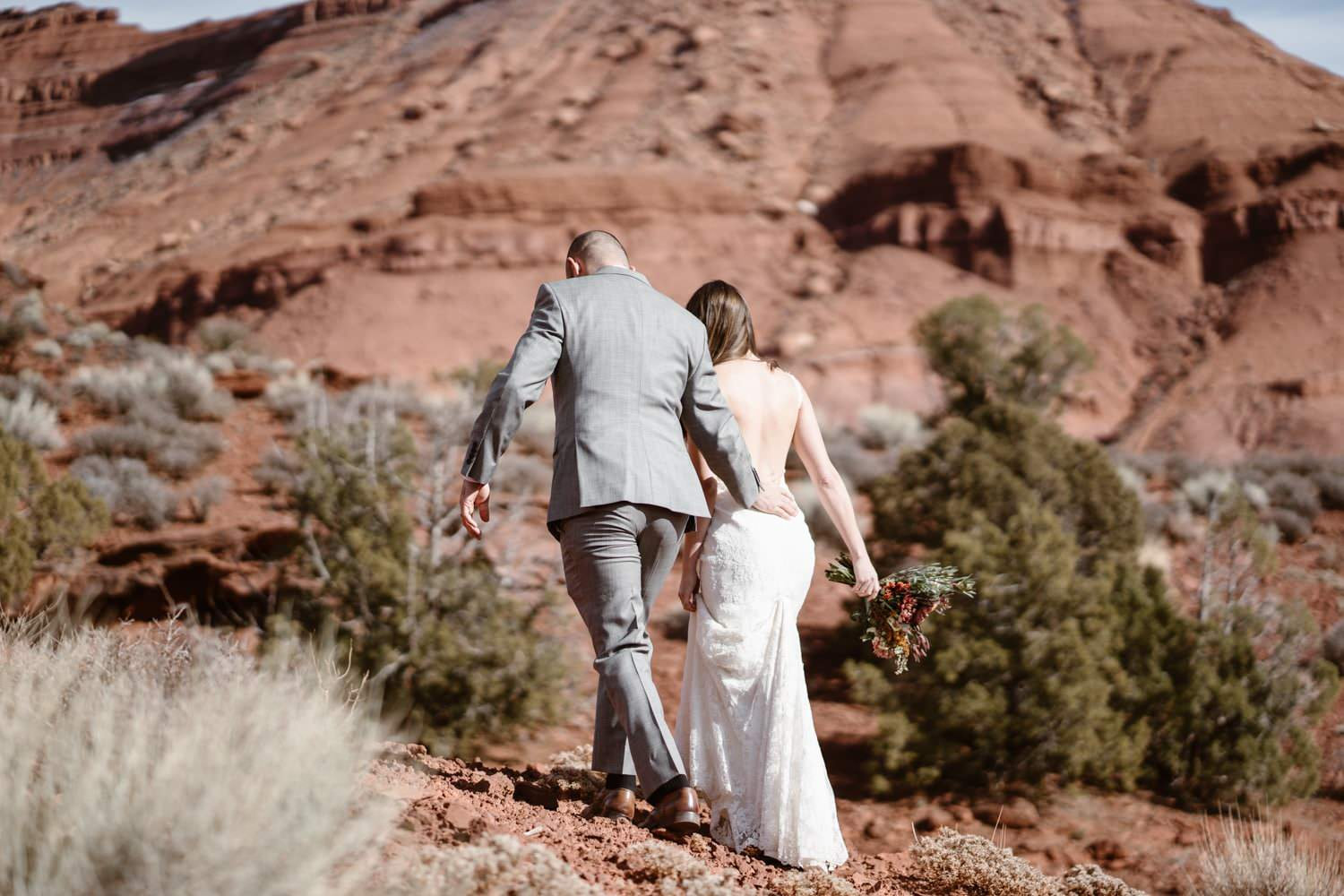 Bride and Groom Hiking During Moab Elopement